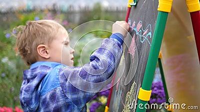 Junge Künstlerin zieht Vorstand Ein Junge unter den Blumen und Pflanzen im Freien zeichnet Kinderbilder mit stock footage