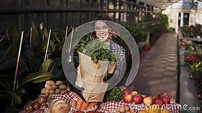 Junge Kaukasierin in Vorhut mit braunem Papierbeutel mit frischem Gemüse und Grün, lächelnd lachen beim posieren stock footage