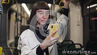 Junge lächelnde Frau, die einen Videoanruf während Transport öffentlich reiten hat Stadt beleuchtet Hintergrund stock video