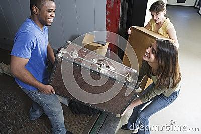 Junge Leute, die schweren Kasten an beweglichem Tag tragen.