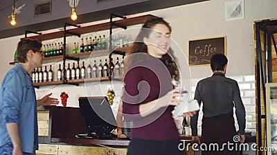 Junge Leute kaufen Kaffee zum Mitnehmen im netten lokalen Café und zahlen mit Smartphone, während freundliche Arbeitskräfte grüße stock footage