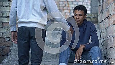 Junge Männer, die sich die Hand ausstrecken, um traurige Freunde zu treffen, die Treppen sitzen, Freundschaftsunterstützung stock video