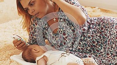 Junge Mutter geben kleine Babyattrappe mutterschaft Smartphone obacht Liebe stock footage