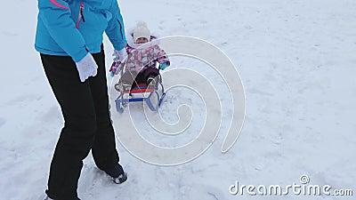 Junge Mutter rollt wenig Baby auf Schlitten entlang schneebedeckter Straße im Winter Kind ist frech und Schreie beim Sitzen im Sc stock video footage
