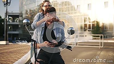 Junge Paare Das Mädchen spielt Vermutung, die Spiel mit ihrem Freund Attraktives männliches Sitzen auf einem Fahrrad Ansicht von  stock video