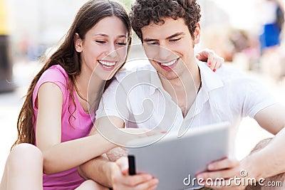 Junge Paare, die digitale Tablette betrachten
