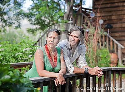 Junge Paare, die an einer kleinen Brücke in einem Garten stillstehen