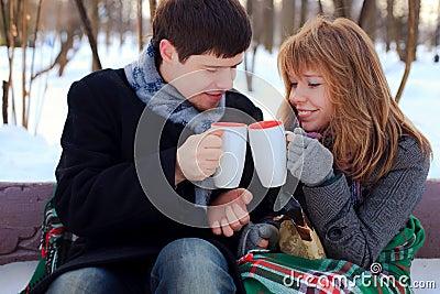 Junge Paare, die im Winterpark sich wärmen
