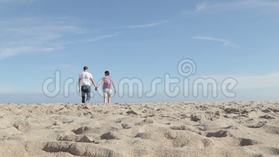 Junge Paare, die zusammen auf dem Strand gehen und sprechen stock footage