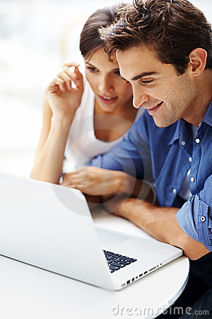 Junge Paare, die zusammen an einem Laptop arbeiten
