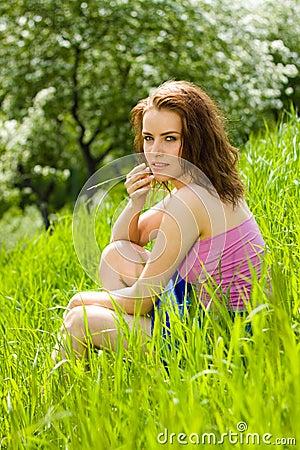Junge schöne Frauen-Träumerei im Gras
