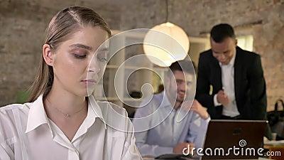 Junge schöne Geschäftsfrau hört, wie ihre Mannkollegen auf Hintergrund über Herm klatschen, Sexismuskonzept stock video footage