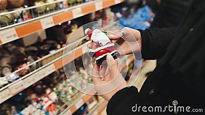 Junge Schönheit, die Andenken für einen Weihnachtsbaum im Speicher auf dem Weihnachtsmarkt wählt Wählen von Weihnachten stock video footage