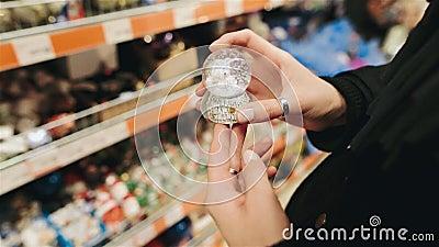 Junge Schönheit, die Andenken im Speicher auf dem Weihnachtsmarkt wählt Wählen von Weihnachtsspielwaren für Baum des neuen Jahres stock video