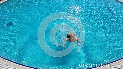 Junge schlanke Frau, die in das Pool springt und unter dem Wasser schwimmt