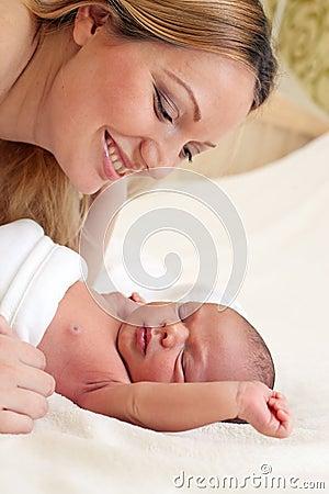 Junge schöne Mutter und neugeborenes Baby