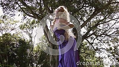 Junge sinnliche Frau mit lockig blonden Haaren in elegantem lila Kleid stock video