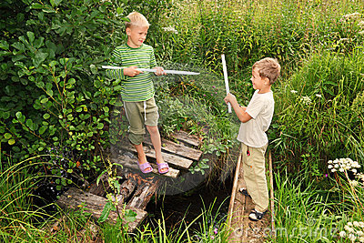 Jungen mit Steuerknüppeln kämpfend um Spaß auf Brücken