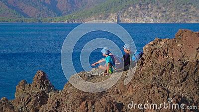 Jungen sitzen auf einem Felsen am Mittelmeer stock video footage