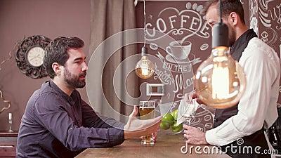 Junger bärtiger Mann erzählt Barmixer und dem Getränkbier eine Geschichte stock video footage