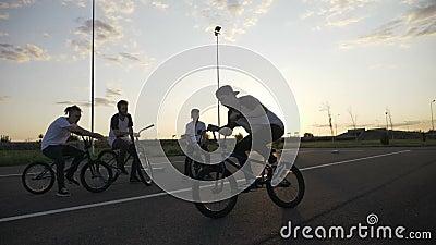 Junger erfahrener Radfahrer, der akrobatische Technik von Rotation 360 mit seinen Freunden draußen in der Zeitlupe übt - stock video footage