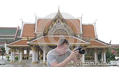 Junger glücklicher touristischer Mann, der um den buddhistischen Tempel in Bangkok fotografiert stock footage