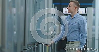 Junger gut aussehender Mann wählt einen Kühlschrank für Kauf Öffnet die Tür und kontrolliert das Gerät, überprüft die Pre stock video
