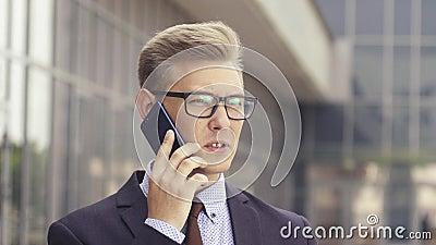 Junger hübscher kaukasischer Geschäftsmann in den Gläsern sprechend am Handy vor Bürogebäude M?nnliches Leitprogramm stock footage