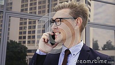 Junger hübscher kaukasischer Geschäftsmann in den Gläsern sprechend am Handy vor Bürogebäude M?nnliches Leitprogramm stock video footage