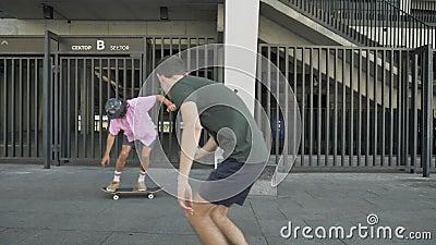 Junger Hippie tut Skateboardtrick in der Tageszeit im Sommer, Mann mit Kamera folgt ihm und tut Video, Sport stock video