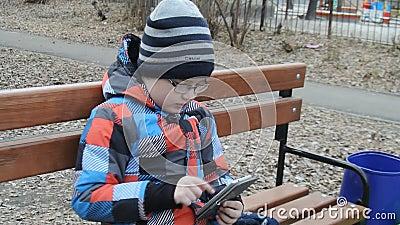 Junger Jugendlicher, der draußen Spiel auf Smartphone auf der Bank spielt stock footage