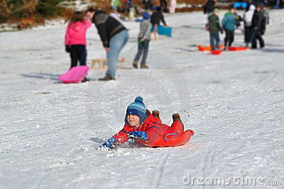 Junger Junge, der schneebedeckten Hügel, Winterspaß schiebt
