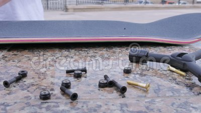 Junger Kerl schraubt die Bolzen in ein Skateboard, das auf der Leiste liegt stock video