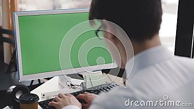 Junger Mann arbeitet mit PC mit grünem Schirm und Tastatur 4K stock video footage