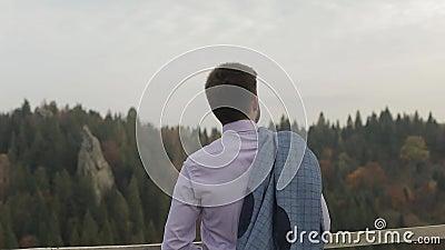 Junger Mann auf dem Hügel eines Berges mit Jacke Geschäftsmann bräutigam groom stock video footage