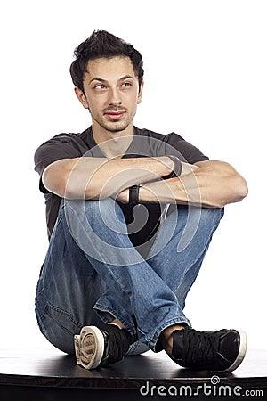 Junger Mann, der auf einer Tabelle sitzt
