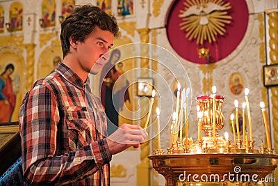 Junger Mann, der eine Kerze in der Kirche beleuchtet.