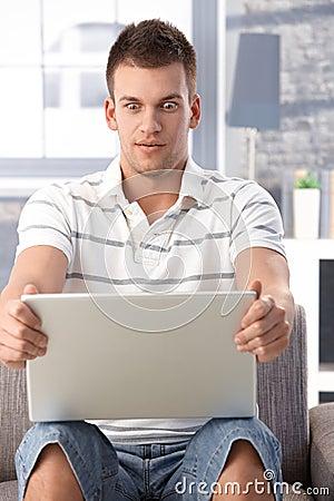 Junger Mann, der entlang des Laptopbildschirms erschrocken anstarrt