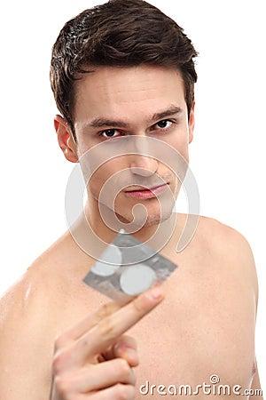 Junger Mann, der Kondom anhält