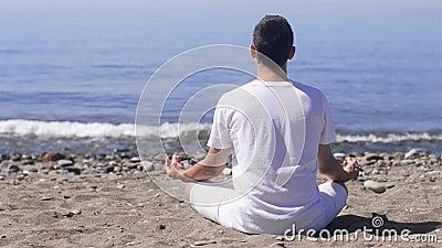 Junger Mann macht Meditation in der Lotoshaltung auf Meer/Ozeanstrand, -harmonie und -betrachtung stock footage