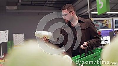 Junger Mann wählt frisches Peking-Kohl im Supermarkt stock video