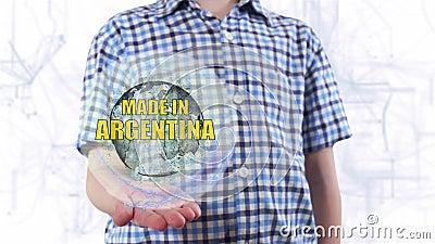 Junger Mann zeigt ein Hologramm der Planetenerde und -textes, die in Argentinien gemacht werden stock footage