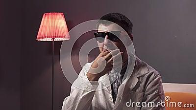Junger netter Mann mit tragender Sonnenbrille des Bartes und weißem Laborkittel toches Schnurrbart stock video footage