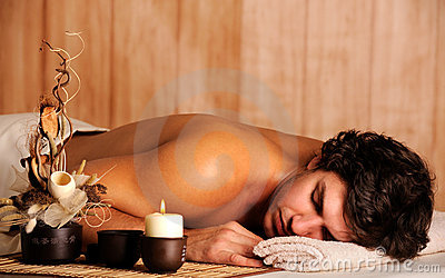 Junger stattlicher Mann, der im Badekurortsalon sich entspannt