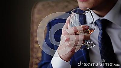 Junger stilvoller Kerl, der ein Glas Whisky hält Abschluss oben cinematic stock video