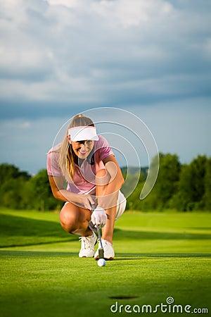 Junger weiblicher Golfspieler auf dem Kurs, der sie anstrebt, setzte sich