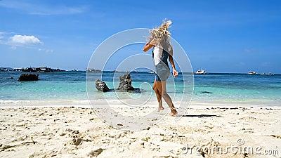 Junges blondes Mädchen läuft entlang den weißen Strand mit Felsen und dem Lächeln Ich fühle mich frei stock video