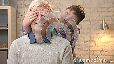 Junges fettes Kind schließt seine großväterlichen ` s Augen mit seinen Händen Vermutung die Ein Spiel, Streich Enkel untersucht d stock video