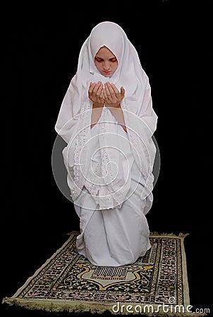 Junges entzückendes islamisches mädchen tragendes hijab und beten