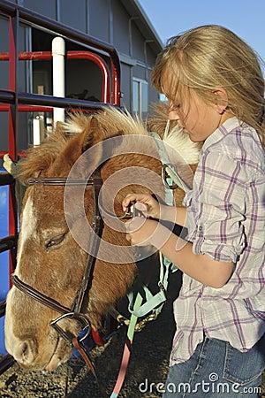 Junges Mädchen, das ihr Pony vorbereitet